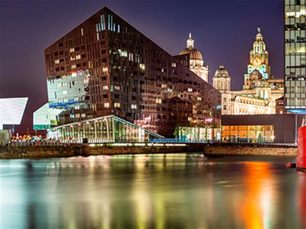 Liverpool at night time with reflection on calm water